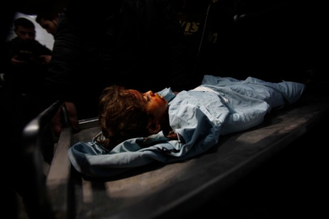 The body of three-years-old Palestinian girl Hala Bhairi, who medics said was killed by shrapnel during an Israeli air strike on the Bureij facility, lies at a hospital morgue in the central Gaza Strip