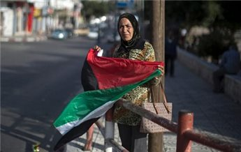 A woman waves the national flag as she celebrates the agreement to form a unity government in Gaza on April 23, 2014. (AFP Mahmud Hams)