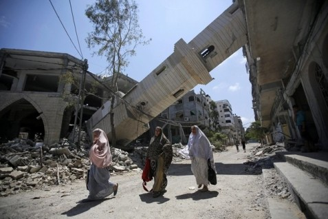 Palestinians walk under the minaret of a destroyed mosque in Gaza. Israel not only are profiting from the reconstruction but also turning the territory into a super-maximum prison. Photo: Mohammed Saber / EPA
