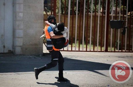 A Palestinian protester carries a wounded comrade during clashes with Israeli forces on May 15, 2014 (MaanImages)