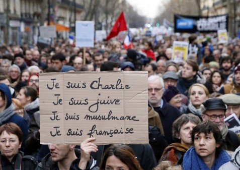 "A woman holds a cardboard sign reading ""Je suis Charlie, je suis Juive, je suis Musulmane, je suis Francaise,"" meaning ""I am Charlie, I am Jewish, I am a Muslim, I am French"" during a unity rally in Paris on Jan. 11. (Photo: Patrick Kovarik/AFP/Getty Images)"