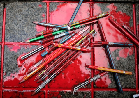 Broken pens were placed in a pool of simulated blood Friday outside the French Consulate in Istanbul in memory of the victims of the shooting at the French satirical newspaper Charlie Hebdo. AP/Emrah Gurel