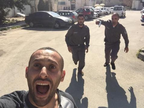 This image appears to show Palestinian rapper Tamer Nafar being pursued by Israeli Defence Force members.
