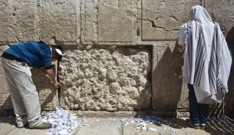 A man prays (R) besides another man who removes notes from the cracks of the Western Wall, Judaism's holiest prayer site, in Jerusalem's Old City March 25, 2015. Photo by Reuters