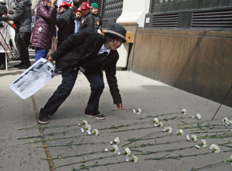 White carnations were left at the foot of the building .. each with the name of a victim attached to it