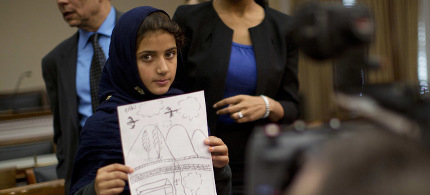 Nabila Rehman, 9, holds up a picture she drew depicting the U.S. drone strike on her Pakistan village (which killed her grandmother Mammana Bibi) at a news conference on Capitol Hill. (photo: Jason Reed/Reuters)
