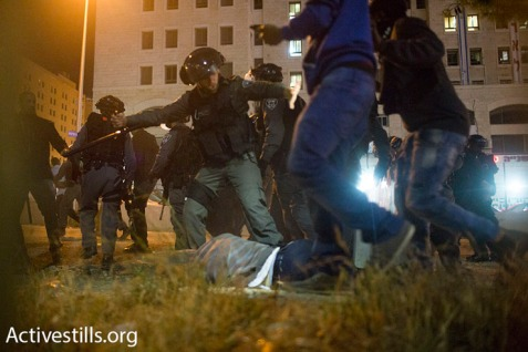 An Israeli police officer uses his baton to attack a protester lying on the ground at a demonstration against police brutality, in Jerusalem on April 30, 2015. (Photo: Oren Ziv/Activestills.org)