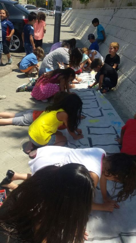 Students and teachers create signs on June 30, 2015, to cover the racist graffiti spray painted on their school's walls the night before. (Courtesy: Hand in Hand)