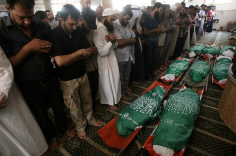 Palestinians pray over the bodies of eight members of the al-Haj family, killed when Israel bombed their Khan Younis house on 10 July 2014. This was one of the attacks investigated by an independent UN body that found extensive evidence of Israeli war crimes during last summer's assault on Gaza. (Eyad Al Baba APA images)