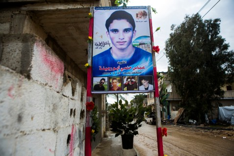 A poster honors the memory of Abbas Helmi Abu Rijeila, 20, seen in the street of Khuzaa, southern Gaza, on 16 November 2014. The business student was killed along with his father and sister in an Israeli missile attack on their home on 27 July 2014. Abbas was killed immediately; his sister Nehad was evacuated on a donkey cart as the ambulance could not reach them. She died a few day later in an Egyptian hospital.