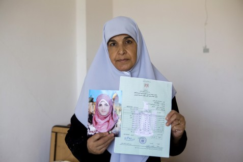 Wafa al-Louh holds a photo of her daughter Eman and her secondary school examination certificate in her home in the central Gaza town of Deir al-Balah on 16 September 2014. Eman was killed in an airstrike on her uncle's nearby home; she was struck in the head by a block of concrete while she was praying next to her bed. Her uncle Mustafa's home, 100 meters from her own, was attacked on 20 August 2014. Eight family members were killed.