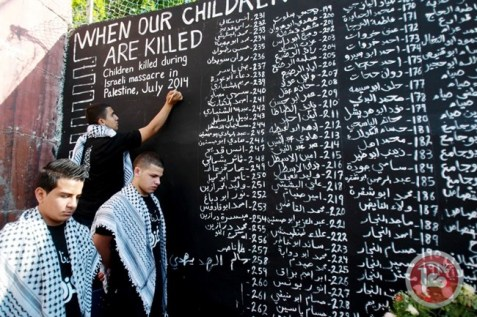 Palestinian youth write the names of children killed during last summer's war in the Gaza Strip. (AFP/ Musa Al Shaer, File)