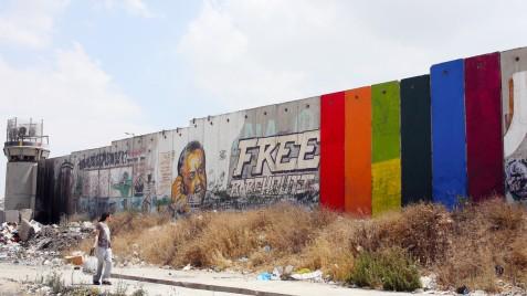 "Khaled Jarrar's rainbow mural ""Through the Spectrum"" painted on the Israeli separation wall near Qalandiya checkpoint in the occupied West Bank. (Khaled Jarrar)"