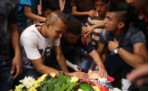 Mourners say farewell to Laith al-Khalidi during his funeral near the West Bank city of Ramallah, 1 August. The teenager died in hospital hours after being shot by Israeli occupation forces near the Atara military checkpoint on 31 July. (Shadi Hatem APA images)