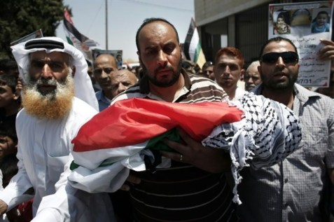 Relatives carry the body of Palestinian toddler Ali Saad Dawabsha, through the streets of the West Bank village of Duma during his funeral on July 31, 2015. (AFP/ Thomas Coex)
