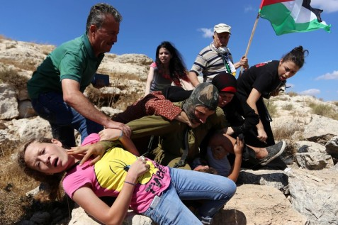 Palestinians intervene to prevent the abduction of a Palestinian boy by an Israeli soldier during a protest against Israeli colonization in the West Bank village of Nabi Saleh, 28 August. (Shadi Hatem APA images)
