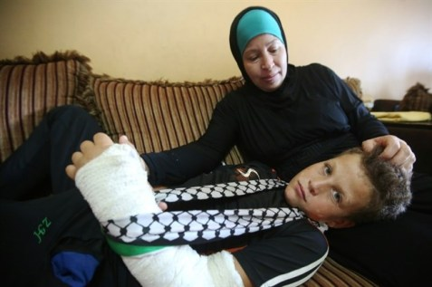 Mohammed Tamimi, 11 years old, rests his head on his mother's lap at their home in the West Bank village of Nabi Saleh near Ramallah, on August 29, 2015. (AFP/Abbas Momani)