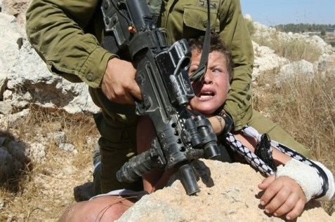 An Israeli soldier pins down 11-year-old Mohammed Tamimi following a march on August 28, 2015 in the West Bank village of Nabi Saleh near Ramallah. (AFP/Abbas Momani)
