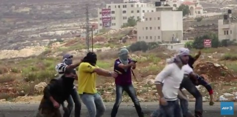 Still from AFP video shows Israeli agents who moments before were posing as demonstrators pull guns on Palestinians.