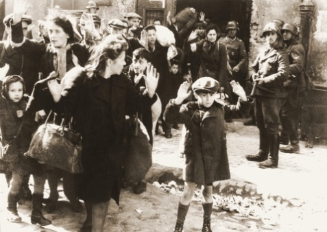 The 'Warsaw Ghetto Boy' This photograph, perhaps the most familiar Holocaust image, shows seven-year-old Tsvi Nussbaum as he raises his hands in Warsaw in 1943.