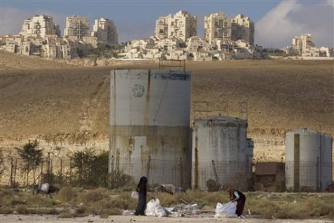 "In this Nov. 22, 2010, photo, Palestinian women collect scrap timber in the Mishor Adumim industrial zone near the Jewish West Bank settlement of Maaleh Adumim. Palestinian advocates contend that multinational companies will need to face ""clear legal and moral liabilities"" for operating in Israeli settlements. (Associated Press)"