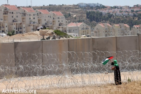 An activist puts a Palestinan flag on the Separation Wall facing the Modi'in Illit settlement (Photo: Anne Paq/ Activestills.org)