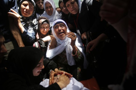 Relatives of Arif Jaradat, a 22-year old who was fatally injured by Israeli occupation forces, mourn over his body during his funeral in Sair village near the West Bank city of Hebron, 20 June. (Nasser Shiyoukhi/ AP Photo)