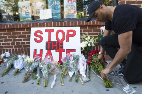 New Yorkers show their solidarity with victims of the massacre at the Pulse nightclub in Orlando, by placing flowers outside The Stonewall Inn, which is considered an epicenter of the US LGBTQ rights movement, in New York's Greenwich Village neighborhood on 12 June. (Albin Lohr-Jones /SIPA)