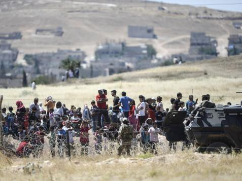 Turkish guards watch over Syrian refugees at the border AFP/Getty Images
