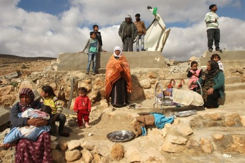 A Palestinian family stands amid the remains of their home after it was demolished by Israeli forces in Masafer Jenbah in an undated photo. (AFP/Hazem Bader, File)