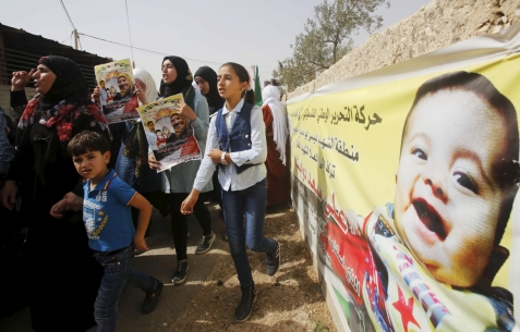 Mourners hold posters of Palestinian Riham Dawabsheh 27 and her family Reuters ... murdered in an arson attack on their home in the summer of 2015. The zio terorists involved were arrested and released.
