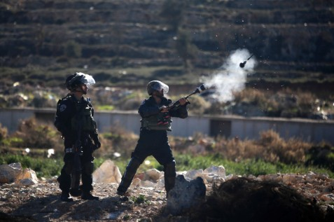 An Israeli soldier fires tear gas towards Palestinian protesters at Beit El on the outskirts of the West Bank city of Ramallah in November 2015. (Shadi Hatem/ APA images)