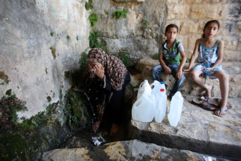 Palestinians collect water from a spring, in the West Bank village of Salfit on 27 June. Villagers had been without water for days as chronic supply shortages induced by Israeli occupation authorities continue to hit many parts of the territory. Nedal Eshtayah APA images