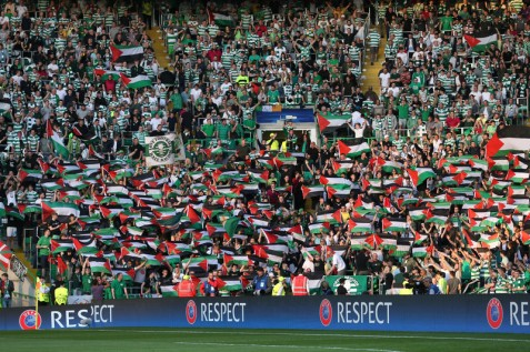 Fans hold up Palestine flags during Glasgow Celtic's match against an Israeli football team on 17 August. (Russell Cheyne/ Reuters)