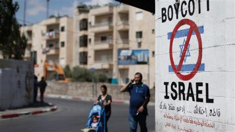 This picture taken on June 5, 2015 shows people walking past a sign painted on a wall in the town of Bethlehem in the south of the Tel Aviv-occupied West Bank on June 5, 2015, calling for a boycott of Israeli products coming from illegal settlements. (Photo by AFP)