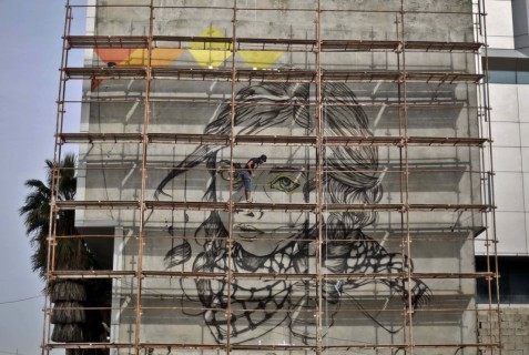 "Belal Khaled at work on the ""Besieged Childhood"" mural in November 2015. Mohammed Talatene/ (APA images)"