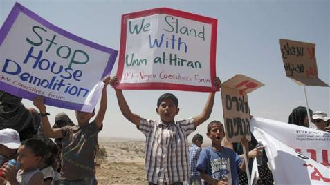 Bedouins hold placards during a protest against a plan to uproot Umm Al-Hiran Village