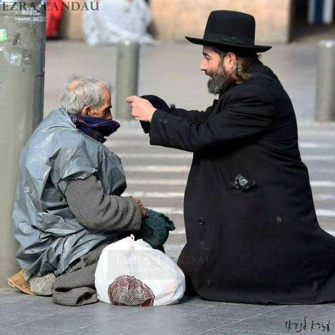 Hope for Jerusalem! An Orthodox Jew puts a wool cap on an old Palestinian this morning in Jerusalem.